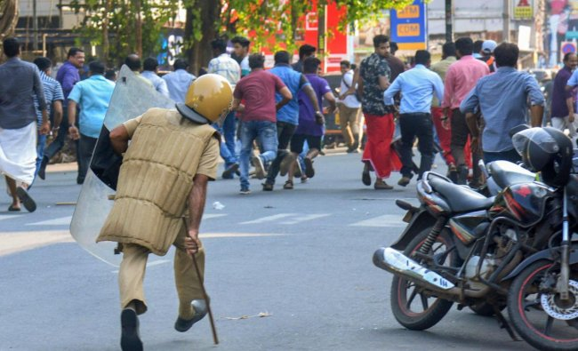 A policeman chases away protesters during a protest against the entry of two women to the Sabarimala temple, in Thiruvananthapuram. PTI