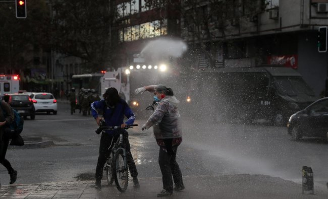 A riot police vehicle releases a jet of water during a protest against Chile\'s government despite social distancing recommended amid the coronavirus disease (COVID-19) outbreak, at Plaza Italia, now known as Plaza de la Dignidad (Dignity square), the main place of rallies since protests broke out in Chile over social injustices and entrenched inequality, in Santiago, Chile. (Reuters photo)