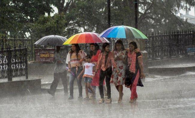 People walk on a road during heavy rainfall, in Shimla on Sunday. PTI Photo