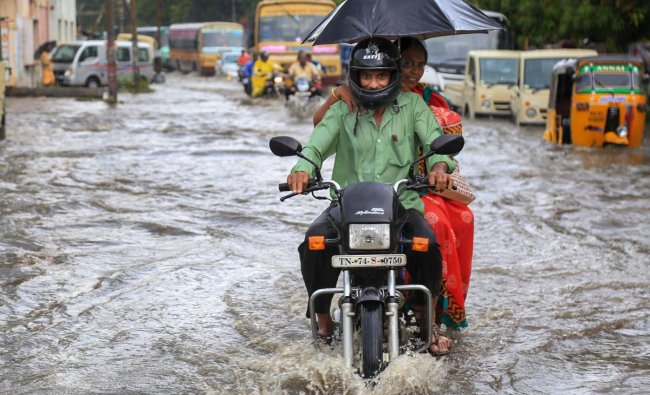 Commuters wade through a waterlogged street following heavy rainfall, in Nagercoil. (PTI photo)