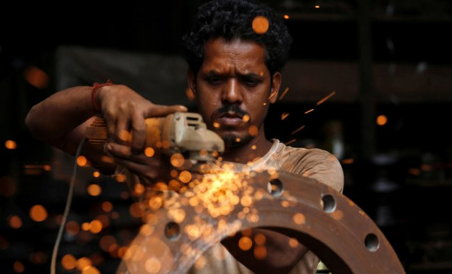 A man uses a disc grinder as he smoothens a flange ring at a workshop in an industrial area in Mumbai, India, August 2, 2018. REUTERS/Francis Mascarenhas