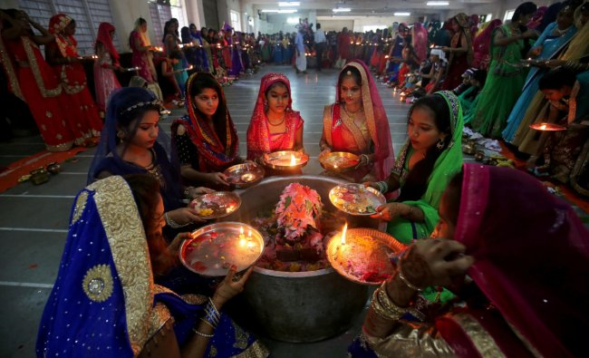 Hindu women perform a ritual known as Aarti around a Shivling (a symbol of Lord Shiva) on the last day of Jaya Parvati Vrat festival, in Ahmedabad, India, July 29, 2018. REUTERS/Amit Dave