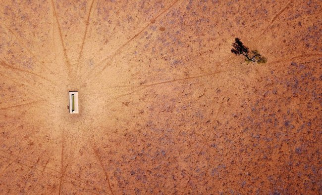 A lone tree stands near a water trough in a drought-effected paddock on Jimmie and May McKeown\'s property located on the outskirts of town of Walgett, in New South Wales, Australia, July 20, 2018. REUTERS/David Gray