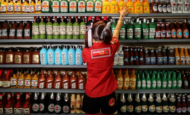British artist Lucy Sparrow, 32, adjusts bottles of alcohol on shelves in her art installation supermarket in which everything is made of felt, in Los Angeles, California, U.S. July 31, 2018. REUTERS/Lucy Nicholson