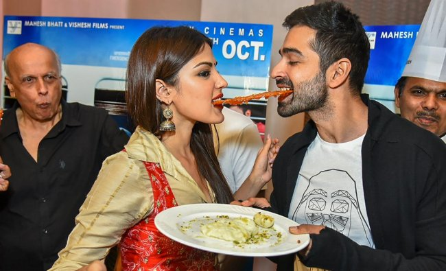 Bollywood actors Rhea Chakraborty and Varun Mitra share a \'jalebi\' during a promotional event for their upcoming movie \'Jalebi\', in New Delhi. (PTI photo)