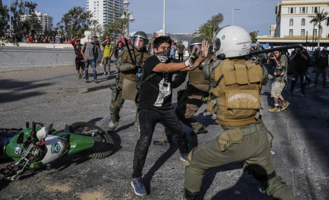 A demonstrator struggles with a riot police during clashes which erupted in a protest against Chile\'s President Sebastian Pinera in the country\'s seaside resort of Vina del Mar. (AFP Photo)