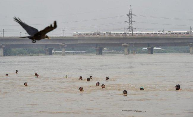 New Delhi: People swim across the swollen Yamuna river, in New Delhi on Sunday, July 29, 2018. (PTI Photo/Manvender Vashist)