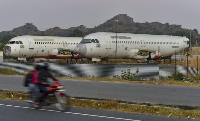 Behror: A biker rides past scrapped passenger planes lying at a yard of a scrap-dealer in Behror, Rajasthan, Friday, Nov 23, 2018. The dealer bought the planes to convert them into restaurants. (PTI Photo/Kamal Kishore)