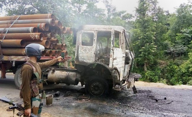 A security person takes pictures of a truck that was torched by the Maoists at Ranchi-Tata highway during their Jharkhand bandh, in Ranchi on Friday. PTI Photo