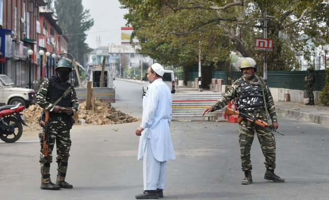 Security personnel stand guard on a road leading to Lal Chowk during restrictions in Srinagar. (PTI)