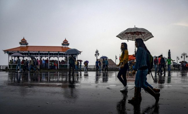 People walk with umbrellas during rain, in Shimla on Friday. PTI Photo