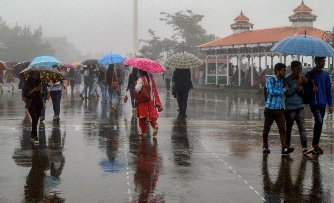 Pedestrians walk under their umbrella during monsoon rainfall, in Shimla on Monday. PTI Photo