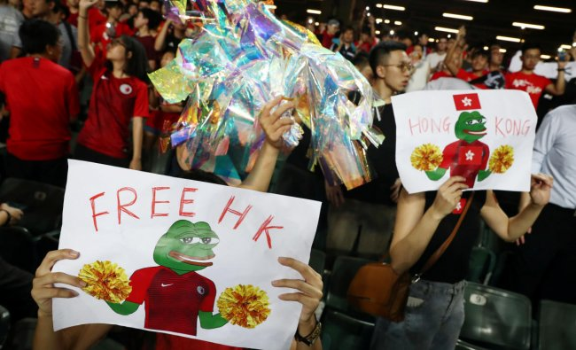 Soccer fans hold placards in support of anti-government protesters during a football World Cup qualifier match between Hong Kong and Iran, at Hong Kong Stadium. (Photo by Reuters)
