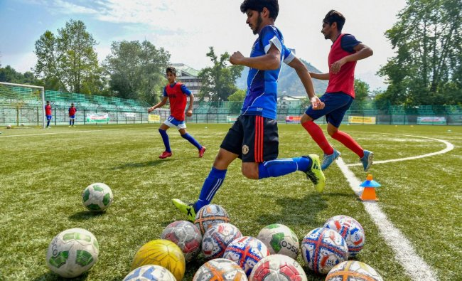A football enthusiast kicks a football during a practice match as FIFA fever grips various parts of the country, in Srinagar. PTI Photo
