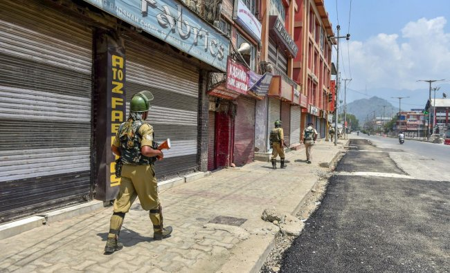 Security personnel patrol a street during a two-day strike called by the separatist leaders against the petitions in the Supreme court challenging the validity of Article 35A, in Srinagar on Sunday. PTI photo