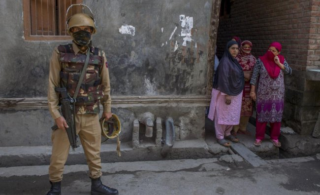 A policeman stands guard after militants shot dead two National Conference workers and injured an office bearer, three days ahead of the first phase of elections for urban local bodies at Karfali Mohalla in Down Town, Srinagar. PTI Photo