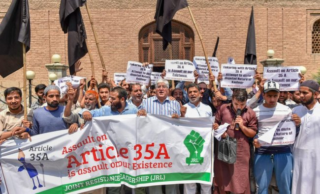 People display placards and wave black flags during a protest against the petitions in the Supreme court challenging the validity of Article 35 A, in Srinagar. PTI Photo