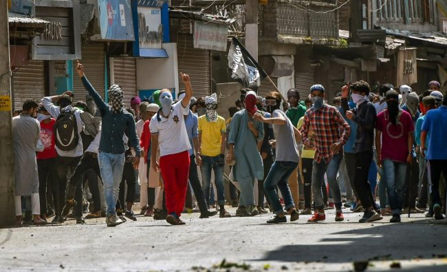 Protesters throw stones at the security personnel during a protest, at Nowhatta, in Srinagar on Friday. PTI Photo
