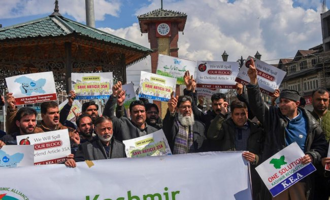 Business community members shout slogans and display placards during a strike call given by the traders in protest against extension of Central laws to Jammu and Kashmir and ban on Jamat-e-Islami, in Srinagar. PTI
