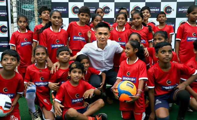Indian footballer Sunil Chhetri poses with children at a promotional event in Mumbai, Friday, June 14, 2019. PTI