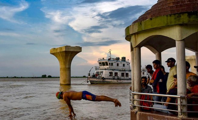 A man jumps into the swollen Ganga river at Gandhi Ghat, in Patna, Saturday, on Aug 24, 2019. (PTI Photo)