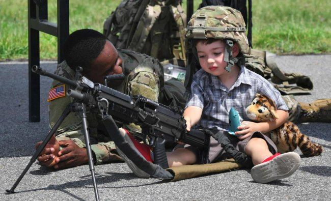 A US soldier looks at a boy posing with a M249 light machine gun during a ceremony to commemorate the 75th anniversary of the Eighth US Army at Camp Humphreys in Pyeongtaek on June 8, 2019. (Photo by Jung Yeon-je / AFP)