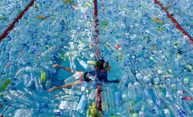 A child swims in a pool filled with plastic bottles during an awareness campaign to mark the World Oceans Day in Bangkok on June 8, 2019. (Photo by Romeo GACAD / AFP)