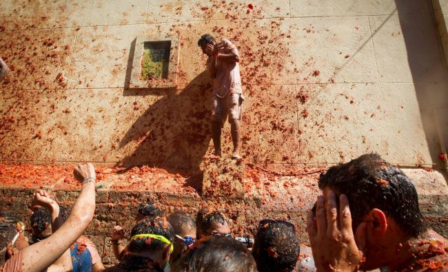 Revellers covered in tomato pulp take part in the annual \