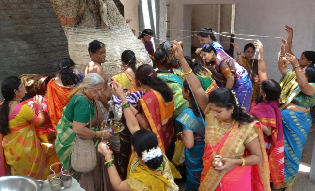 Married women tie threads around a tree and offer prayers in the honor of their husbands on the occasion of \'Vat Savitri Puja\' festival in Solapur, Sunday, June 16, 2019. PTI