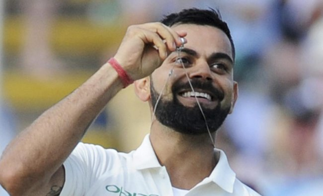 Indian cricket captain Virat Kohli holds up his wedding ring as he celebrates scoring a century during the second day of the first test cricket match between England and India at Edgbaston in Birmingham, England. AP/PTI Photo