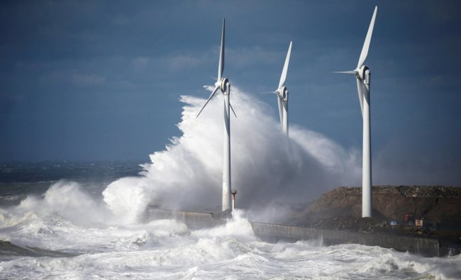 Waves crash against power-generating windmill turbines during a windy day in Boulogne-sur-Mer, France, March 10, 2019. REUTERS/Pascal Rossignol