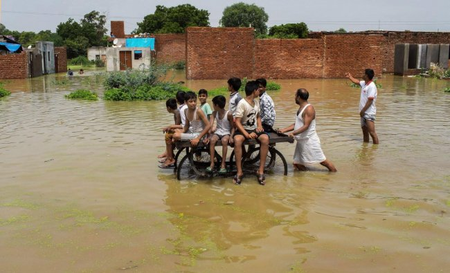 Mathura: Children ride a cart as they move through a flooded colony, inundadted by the Yamuna river, in Mathura on Thursday, Aug 2, 2018. (PTI Photo)