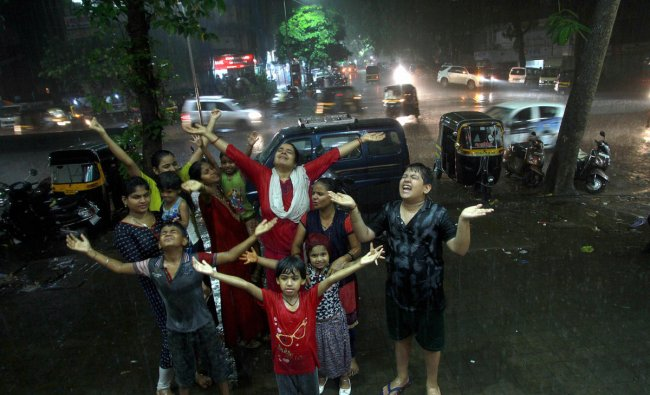 People enjoy the first shower of the season in Thane, Monday night, June 10, 2019. (PTI Photo)