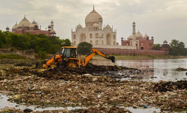 An earthmover removes debris from the Yamuna river bed against the background of Taj Mahal, in Agra, Sunday, June 16, 2019. PTI