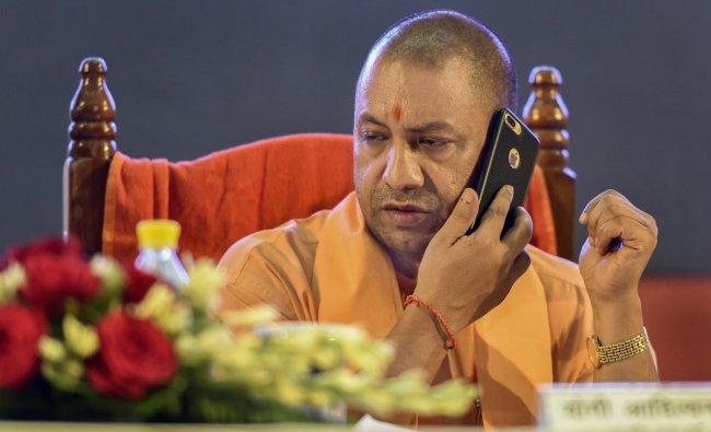 Uttar Pradesh Chief Minister Yogi Adityanath talks on a phone during an event, in Lucknow on Monday. PTI Photo