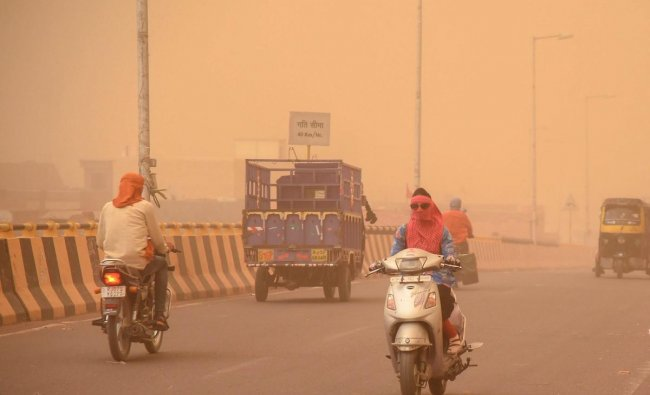Commuters ride on a road during a dust storm, in Bikaner on Sunday. PTI Photo