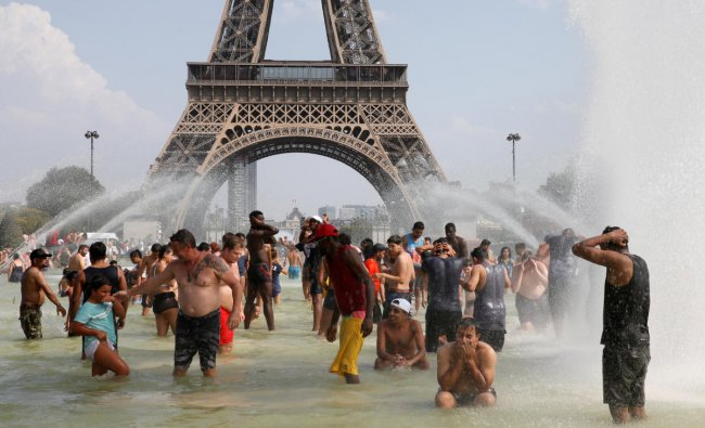 People cool off in the Trocadero fountains across from the Eiffel Tower in Paris as a new heatwave broke temperature records in France. (Reuters Photo)
