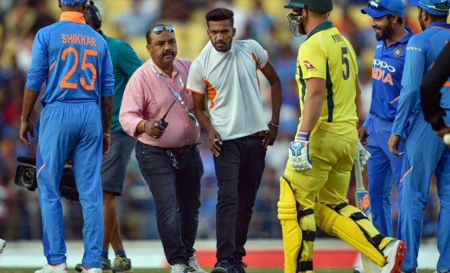 A security person tackles a pitch-invader who ran to the playing area to greet MS Dhoni during the 2nd ODI cricket match against Australia at Vidarbha Cricket Association Stadium in Nagpur. PTI