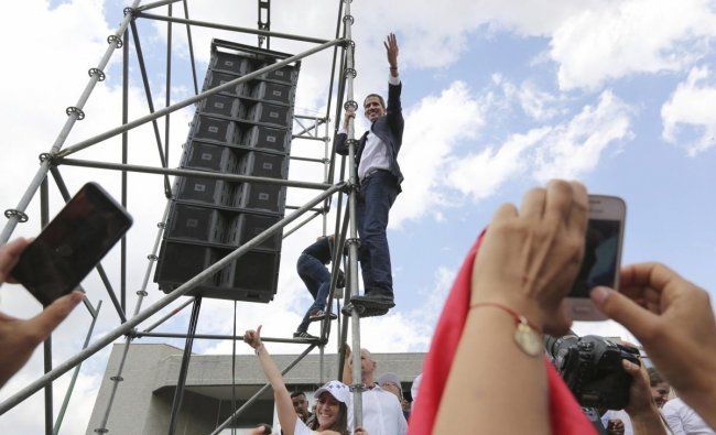 Venezuelan Congress President Juan Guaido, an opposition leader who declared himself interim president, waves from the scaffolding after speaking at a rally demanding the resignation of Venezuelan President Nicolas Maduro in Caracas, Venezuela. AP/PTI
