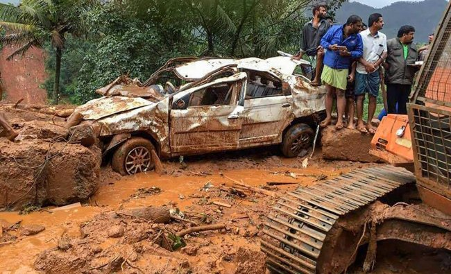 People inspect a damaged car following a landslide, triggered by heavy rains, in Idukki, Kerala on Thursday. PTI photo