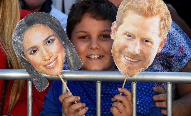 A boy holds the masks of Prince Harry and his wife Meghan, the Duke and Duchess of Sussex, before their arrival to the District Six Museum, on the first day of their African tour in Cape Town, South Africa, September 23, 2019. REUTERS/Toby Melville