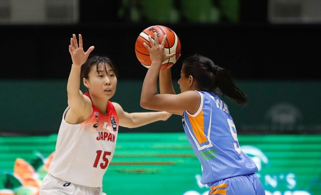 Japan\'s Nako Motohashi (L) attempts to stop the ball from India\'s Madhu Kumari during the 2019 FIBA Women\'s Asia Cup basketball match between Japan and India in Bangalore on September 24, 2019. (Photo by Abhishek N. CHINNAPPA / AFP)
