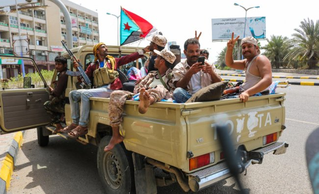 Fighters of the UAE-trained Security Belt Force, dominated by members of the Southern Transitional Council (STC) which seeks independence for south Yemen, flash the victory gesture as they sit with a southern separatist flag (the old flag of South Yemen) in the back of a pickup truck near the Aden Hotel in the Khor Maksar district of the second city of Aden on August 29, 2019. (Photo by Nabil HASAN / AFP)
