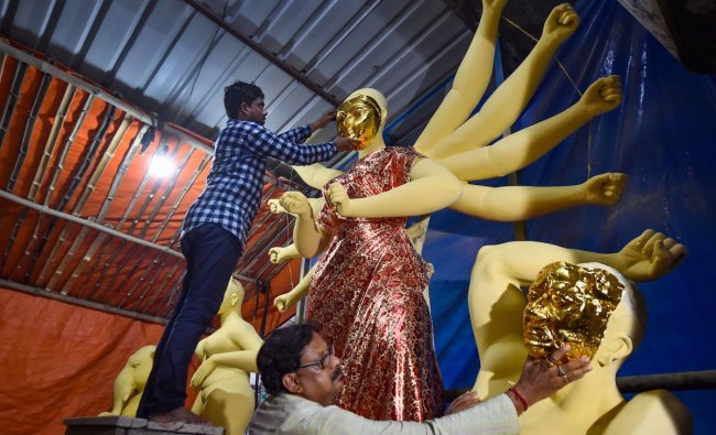 Kolkata: Clay artist Mintu Paul and his associates take measurements to adjust gold mask on the clay idol of Goddess Durga at a workshop before being transported to a community pandal, ahead of Durga Puja festival in Kolkata, Thursday, Sept. 26, 2019. (PTI Photo/ Swapan Mahapatra)(PTI9_26_2019_000177B)