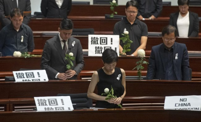 Pro-democracy lawmakers pay a silent tribute to the man who fell to his death on Saturday evening after hanging a protest banner on scaffolding on a shopping mall, at the Legislative Council in Hong Kong, Wednesday, June 19, 2019. AP/PTI