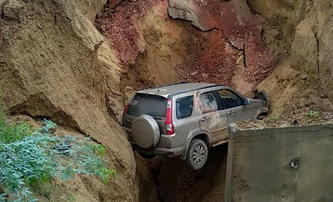 Agra: A vehicle trapped in a ditch at a damaged service road of the Agra- Lucknow Expressway near Agra on Wednesday, Aug 1, 2018. (PTI Photo)