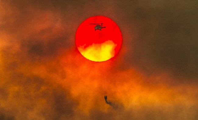 Redding : In this Friday, July 27, 2018 photo, a firefighting helicopter makes a water drop as the sun sets over a ridge burning near Redding, Calif., in efforts against the Carr Fire. Scorching heat, winds and dry conditions complicated firefighting efforts. AP/ PTI