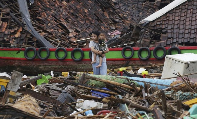 A man holds a child as he surveys the damage at a village struck by a tsunami in Sumur, Indonesia, Tuesday, Dec. 25, 2018. The waves struck without warning three days earlier. AP/PTI