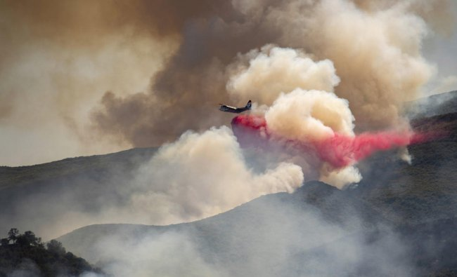 A plane drops fire retardant on a hillside in an attempt to box in flames from a wildfire during the Sand Fire in Rumsey, Calif., Sunday, June 9, 2019. AP/PTI(