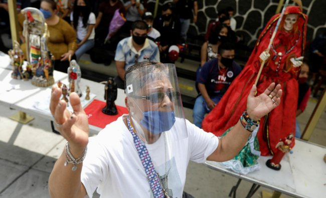 A man wearing protective face mask and face shield prays during a mass on the first day of the reopening of the temple of the cult figure La Santa Muerte (The Saint of Death) after government restrictions were eased, amid the coronavirus disease (COVID-19) outbreak in Tultitlan, on the outsides of Mexico City, Mexico. Credit/Reuters Photo